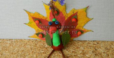 Павлин из каштанов и осенних листьев